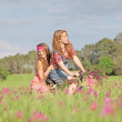 Happy girls riding bike or bicycle in summer meadow — Stock Photo