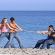 Tug of war, teens playing on beach on summer vacation or spring break — Stock Photo