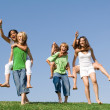 Group of kids at summer camp or school having piggyback race. — Stock Photo