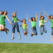 Foto de Stock  : Happy group of mixed race kids at summer camp or school jumping