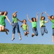 Happy group of mixed race kids at summer camp or school jumping - Foto Stock
