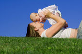 Happy mother or mum playing with baby girl — Stockfoto