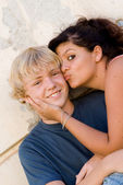 Young teen couple girl kissing boy — Stock Photo