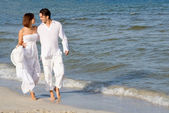 Young honeymoon, couple walking on beach on summer holiday or vacation — Stock Photo