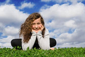 Happy healthy teen sitting on grass outdoors in summer — Stock Photo