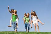 Grupy dzieci w obozie letnim lub w szkole o piggyback wyścigu. — Zdjęcie stockowe