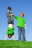 Twins, twin brothers playing outside, in summer one upside, down. — Stock Photo