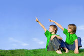 Kids or children pointing at copy space outdoors in summer — Stock Photo