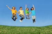 Fit healthy children jumping outdoors in summer — Stock Photo