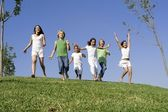 Group of happy kids at summer camp or school running or racing — Stock Photo