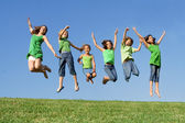 Happy group of mixed race kids at summer camp or school jumping — ストック写真