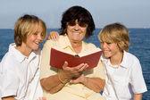 Grandmother, reading book to grandchildren — Stock Photo