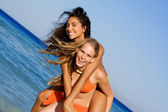 Piggyback girls on beach summer vacation or holiday or at spring break — Stock Photo