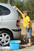 Kid playing having fun cleaning or washing car — Stock Photo