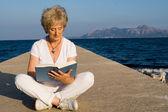 Senior vrouw zittend op strand boek lezen op zomervakantie in mallorca — Stockfoto
