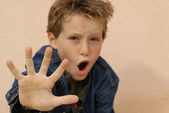 Defiant or abused boy angry or frightened hand out — Stock Photo