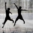 Silhouette of kids jumping in cool fountain water — Stockfoto