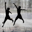 Silhouette of kids jumping in cool fountain water - Foto de Stock