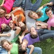 Group of happy healthy kids laying outdoors on grass at summer camp - Stock Photo