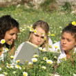 Group of healthy happy girls reading in flower field — Stock Photo