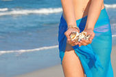 Woman on beach on summer vacation collecting shells — Stock Photo