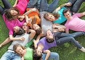 Group of happy healthy kids laying outdoors on grass at summer camp — Stock Photo