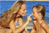 Zon zorg, moeder zonnebrandcrème zetten kind — Stockfoto