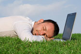 Business man relaxing having power nap outdoors with computer laptop — Stock Photo