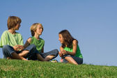Kids or children sitting outside on grass chatting, — Stock Photo