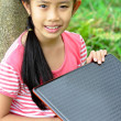 Young girl posing in park with a laptop — Stock Photo