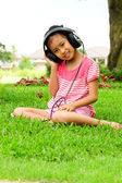 A young asian school girl listening to music online — Stock Photo