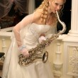 Bride plays the saxophone — Stock Photo #6568487