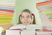 School girl sitting at the table with stacks of books — Stockfoto
