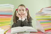 Bored school girl sitting at the table with stacks of books — Stock Photo