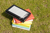 Ebook reader with a stack of books — Stock Photo