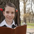 Teen girl with the Bible in a park — Stock Photo