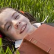 Girl with the Bible laying on the grass — Stock Photo