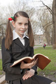 Teen girl with a book in a park — Stock Photo