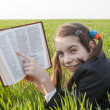 Girl with the Bible laying on the grass — Stock Photo #5523425