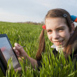 Teen girl with e-book reader laying on grass — Stock Photo #5523440
