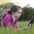 Teen girl reads elecctronic book laying on grass — Stock Photo #5584613