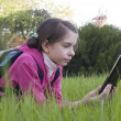 Teen girl reads elecctronic book laying on the grass — Stock Photo #5584613