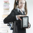Teen girl with electronic book with a stack of printed books behind — Stock Photo