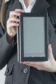 Girl holding an electronic book reader — Stock Photo