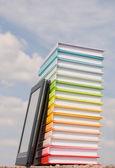 Pile de livres colorés et lecteur de livre électronique à l'extérieur — Photo