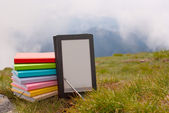 Stack of colorful books and electronic book reader on the grass — Stock Photo