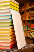 Book with white cover staying at stack of colorful books — Stock Photo