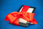 Electronic book reader tied up with a red ribbon — Stock Photo