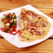 Omelet with prosciutto ham and rocket salad. - Foto Stock
