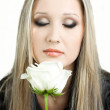 Beautiful young blond woman with a flower in her hands — Stock Photo